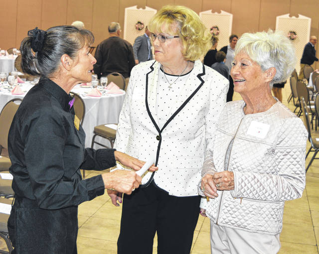 One of this year's Outstanding Women of Clinton County, Sandy Pidgeon, right, speaks with from left, a Roberts Convention Centre staffer and an event guest.