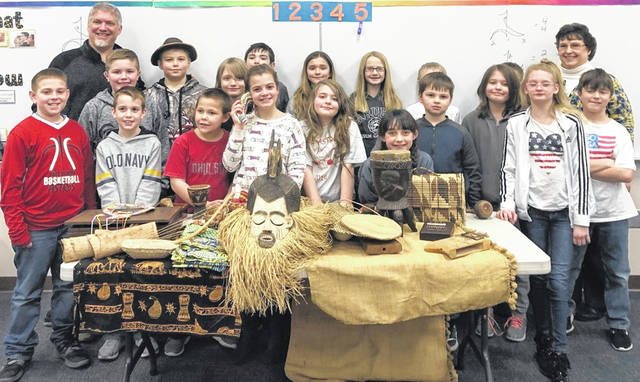From left in the first row are Brendon Barber, Carson Carey, Conner Hornschemeier, Isabelle Hale, Madi Purdin, Grace Wiseman, Austyn Clark, and Aleia Kell; from left in the second row are Wade Smith, Colt Riehle, Malachi Lutz, Kaiden Roth, Sahara Tate, Mallory Thomason, Aiden McQueen (mostly hidden), Tempa Helterbran, Brody Looper (mostly hidden), and Jackson Fish; and the two adults in the back from left are Heifer International advocate Eric Smith and New Vienna Elementary fourth-grade teacher Rita Murphy.