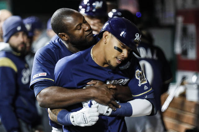 Milwaukee Brewers' Orlando Arcia, right, celebrates in the dugout with Lorenzo Cain, left, after hitting a three-run home run off Cincinnati Reds relief pitcher Michael Lorenzen in the sixth inning of a baseball game, Tuesday, April 2, 2019, in Cincinnati. (AP Photo/John Minchillo)