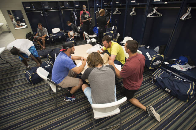 "FILE - In this April 8, 2015, file photo, members of the Biloxi Shuckers minor league baseball team eat lunch before practice at the Pensacola Blue Wahoos' stadium in Pensacola, Fla. Minor leaguers at the lowest levels can make as little as $1,100 per month despite spending 50-to-70 hours per week at the ballpark. A lawsuit alleging MLB violated minimum wage and overtime requirements was pre-empted in 2018 when Congress passed the ""Save America's Pastime Act,"" which stripped minor leaguers of the protection of federal minimum wage laws. (AP Photo/Michael Spooneybarger, File)"