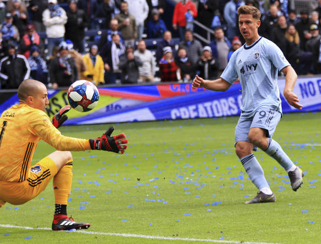 Sporting Kansas City forward Krisztian Nemeth, right, chips the ball over Montreal Impact goalkeeper Evan Bush, left, for his third goal of the match Saturday, March 30, 2019, during an MLS match in Kansas City, Mo. (Ryan Weaver/The Kansas City Star via AP)