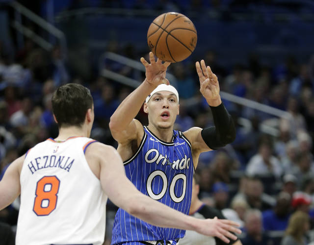 Orlando Magic's Aaron Gordon (00) passes the ball over New York Knicks' Mario Hezonja (8) during the second half of an NBA basketball game Wednesday, April 3, 2019, in Orlando, Fla. (AP Photo/John Raoux)