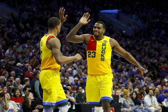 Milwaukee Bucks' George Hill, left, and Sterling Brown celebrate during the second half of the team's NBA basketball game against the Philadelphia 76ers, Thursday, April 4, 2019, in Philadelphia. Milwaukee won 128-122. (AP Photo/Matt Slocum)