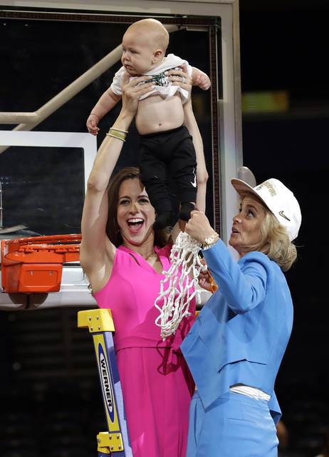 Baylor coach Kim Mulkey, right, watches as her daughter and assistant coach Makenzie Fuller holds up her 6-month-old son Kannon Reid Fuller, after the Final Four championship game against Notre Dame in the NCAA women's college basketball tournament Sunday, April 7, 2019, in Tampa, Fla. Baylor won 82-81. (AP Photo/Chris O'Meara)