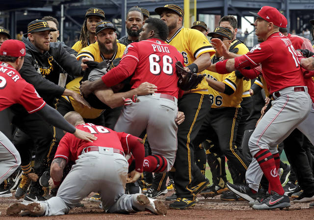 Cincinnati Reds' Yasiel Puig (66) is restrained by Pittsburgh Pirates bench coach Tom Prince, in the middle of a bench clearing brawl during the fourth inning of a baseball game in Pittsburgh, Sunday, April 7, 2019. (AP Photo/Gene J. Puskar)