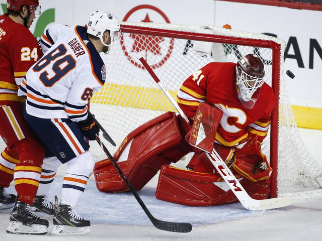 Edmonton Oilers' Sam Gagner, left, has his shot deflected by Calgary Flames goalie Mike Smith during the first period of an NHL hockey game Saturday, April 6, 2019, in Calgary, Alberta. (Jeff McIntosh/The Canadian Press via AP)