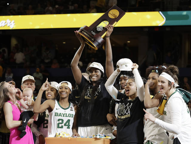 Baylor center Kalani Brown holds the championship trophy next to guard Chloe Jackson (24) after Baylor defeated Notre Dame 82-81 in the final of the NCAA women's college basketball tournament Sunday, April 7, 2019, in Tampa, Fla. (AP Photo/Chris O'Meara)