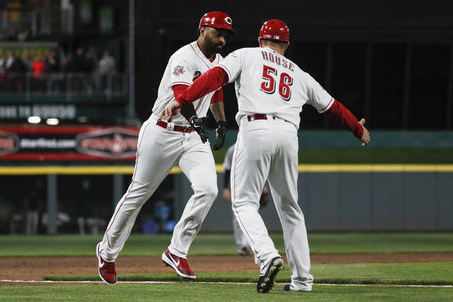 Cincinnati Reds' Matt Kemp, left, celebrates with third base coach J.R. House (56) while running the bases on his three-run home run off Miami Marlins pitcher Wei-Yin Chen during the sixth inning of a baseball game Tuesday, April 9, 2019, in Cincinnati. (AP Photo/John Minchillo)