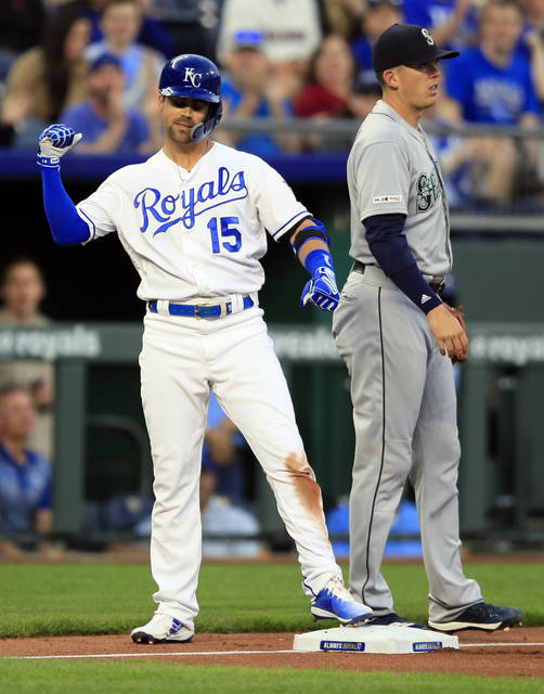 Kansas City Royals' Whit Merrifield (15) celebrates at third base after hitting a triple off Seattle Mariners starting pitcher Marco Gonzales during the first inning of a baseball game at Kauffman Stadium in Kansas City, Mo., Tuesday, April 9, 2019. With that hit Merrifield tied George Brett with a team record for hits in consecutive games. (AP Photo/Orlin Wagner)