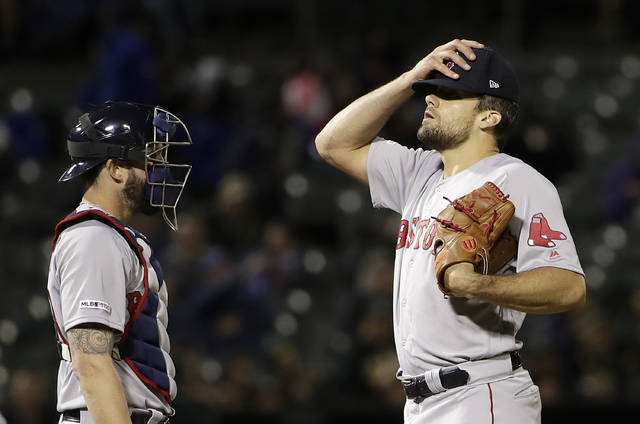 Boston Red Sox pitcher Nathan Eovaldi, right, reacts next to catcher Blake Swihart after walking Oakland Athletics' Marcus Semien to load the bases during the second inning of a baseball game in Oakland, Calif., Wednesday, April 3, 2019. (AP Photo/Jeff Chiu)
