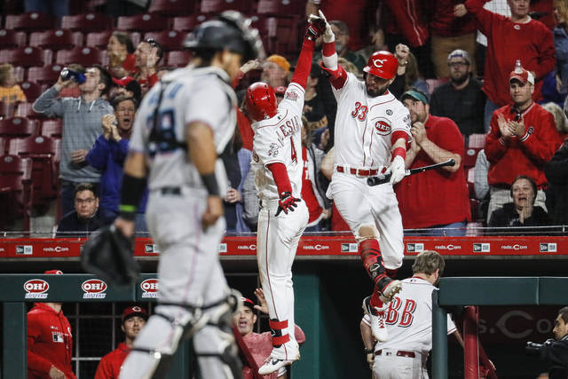 Cincinnati Reds' Jose Iglesias (4) celebrates his game-tying solo home run with Jesse Winker (33) in the eighth inning of a baseball game against the Miami Marlins, Wednesday, April 10, 2019, in Cincinnati. (AP Photo/John Minchillo)