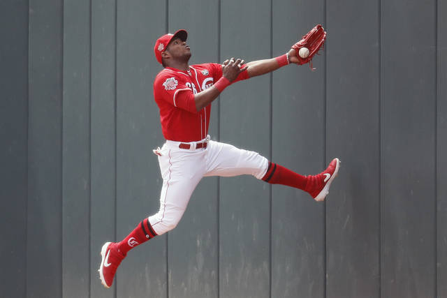 Cincinnati Reds right fielder Yasiel Puig catches out Miami Marlins' Curtis Granderson in the first inning of a baseball game, Thursday, April 11, 2019, in Cincinnati. (AP Photo/John Minchillo)