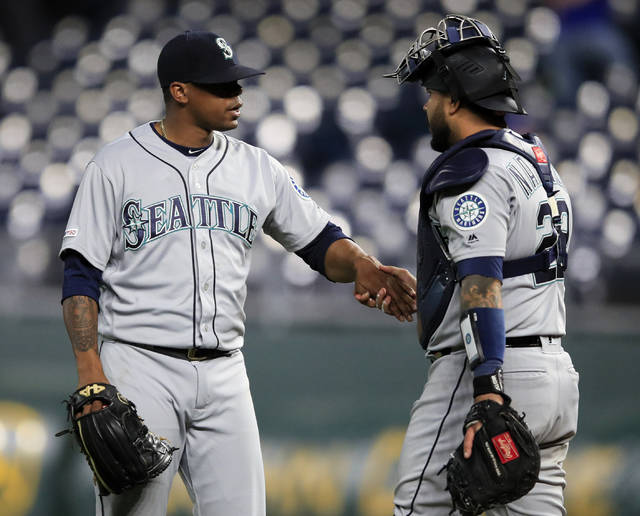 Seattle Mariners relief pitcher Roenis Elias, left, is congratulated by catcher Omar Narvaez following the team's baseball game against the Kansas City Royals at Kauffman Stadium in Kansas City, Mo., Wednesday, April 10, 2019. The Mariners defeated the Royals 6-5. (AP Photo/Orlin Wagner)