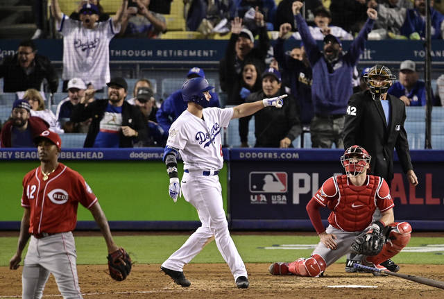 Los Angeles Dodgers' Joc Pederson, center, points toward his dugout as he hits a walk-off, two-run home run as Cincinnati Reds relief pitcher Raisel Iglesias, left, and catcher Curt Casali watch during the ninth inning of a baseball game, Monday, April 15, 2019, in Los Angeles. (AP Photo/Mark J. Terrill)