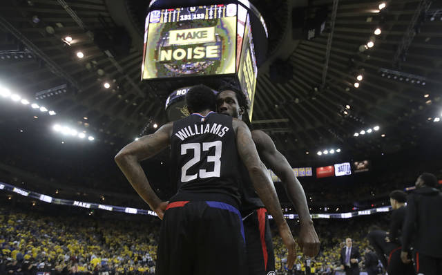 Los Angeles Clippers guard Lou Williams (23) celebrates with Patrick Beverley during the second half of Game 2 of a first-round NBA basketball playoff series against the Golden State Warriors in Oakland, Calif., Monday, April 15, 2019. (AP Photo/Jeff Chiu)