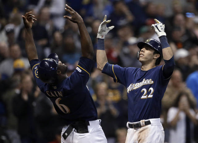 Milwaukee Brewers' Christian Yelich (22) celebrates with Lorenzo Cain (6) after hitting a three-run home run during the fifth inning of the team's baseball game against the St. Louis Cardinals on Tuesday, April 16, 2019, in Milwaukee. (AP Photo/Aaron Gash)