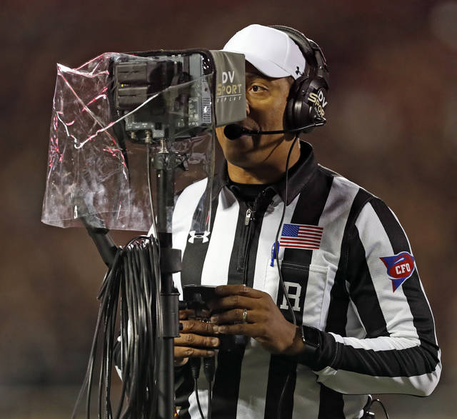 """FILE - In this Nov. 3, 2018, file photo, referee Reggie Smith reviews a targeting penalty during the first half of an NCAA college football game in Lubbock, Texas. The NCAA Playing Rules Oversight Panel adjusted the targeting rule in college football, allowing video review officials to overturn calls if any element of the penalty cannot be confirmed. The adjustment to the rule announced Tuesday, April 23, 2019, means there will be no option for letting the call on the field """"stand"""" during a targeting review. It must either be confirmed or overturned. (AP Photo/Brad Tollefson, File)"""