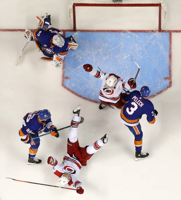 Carolina Hurricanes right wing Nino Niederreiter, bottom, of Switzerland, falls back while celebrating his third-period goal with teammate center Jordan Staal, center, during the third period of Game 2 of an NHL hockey second-round playoff series against the New York Islanders, Sunday, April 28, 2019, in New York. Islanders goaltender Robin Lehner (40), of Sweden, center Brock Nelson (29) and defenseman Adam Pelech (3) look on during the celebration. The Hurricanes won 2-1. (AP Photo/Julio Cortez)