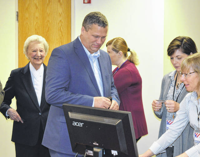 County Commissioner Mike McCarty shows his ID and becomes the second Clinton Countian to cast a ballot in the May primary.