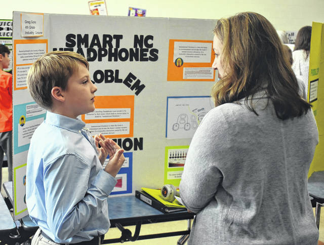 Fourth-grader Greg Goins, left, tells Jill Binau about his idea of smart noise-canceling headphones during Clinton Massie's-Invention Convention on Wednesday.