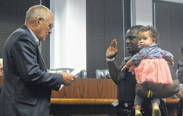 Michael Bower, right, holds his daughter, Brooklyn, as Mayor John Stanforth swears him in as Wilmington's newest police officer during Thursday's Wilmington City Council meeting.