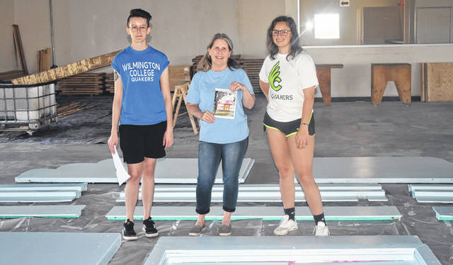 From left, Wilmington College students Molly Howard, Betty Caudill, and Madison Wellendorf stand among their next big project — repainting the Banana Split Festival's facade to resemble how it looked 25 years ago. The students got the opportunity after their professor, Hal Shunk, presented it to them during class one day.