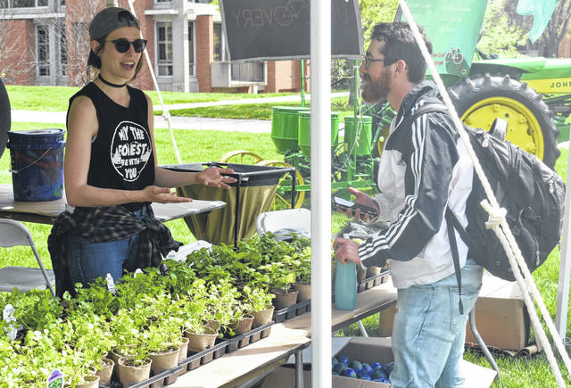 Keni Brown, left, talks to Logan Dyer about how he can reduce his own carbon footprint and the benefits of planting his own cilantro or basil during Wilmington College's DisCO2very Earth Day event on Tuesday.
