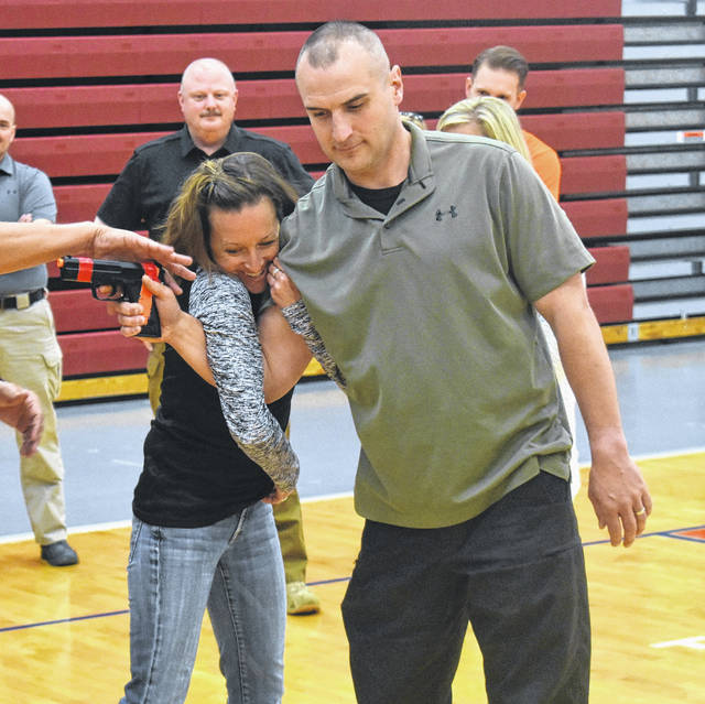 Annie Kennedy, left, of North Olmsted Schools and Brian Fletcher of the Batavia Police Department take part in an exercise to overpower a potential gunman during the second day of the ALICE training session on Wednesday at Clinton-Massie High School.
