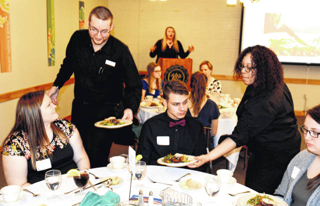 Senior Lindsay Burton and sophomore Abe Werle are served by Sodexo's Aspen Galloway and Daniel Kagarise, operations manager.