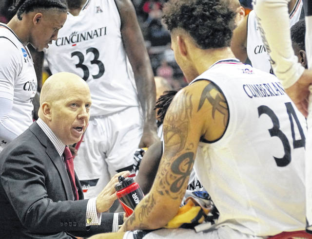 Mick Cronin (left) during a timeout in Cincinnati's NCAA tournament game against Iowa. At the right is Wilmington High School graduate and UC junior Jarron Cumberland (34). Cronin is leaving Cincinnati take the head coaching job at UCLA.