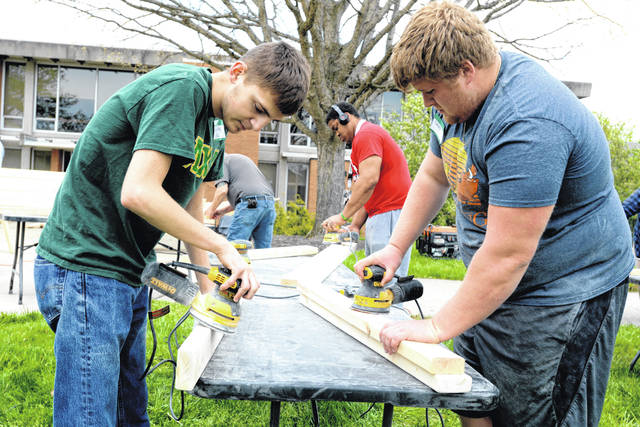 From left, WC students Gabe King, Donovan Hayes and Caleb Deaver sand boards that will be used to make bunk-beds during WC's 26th annual day of community service.