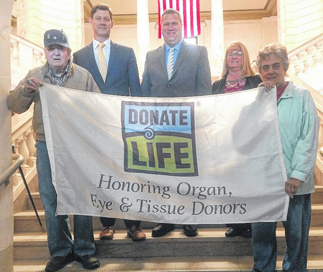 "County commissioners proclaim April as ""Donate Life Month"" on the courthouse stairs Monday. Holding the banner are Frank and Barb Jones. The Joneses are grandparents of organ donor Luke LaPine, who died in June 2014. From left in the back are Commissioners Kerry Steed, Mike McCarty and Brenda Woods."