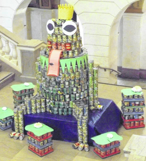 As part of the CANstruction 2019 food drive, employees at the Clinton County Courthouse built a large frog on the staircase landing of the 100-year-old building. The canned goods that were utilized in the various CANstruction projects will end up in the Clinton County homeless shelter food pantry. The frog's body consists largely of cans of peas and green beans. Given the crown on top of the frog's head, the frog apparently once upon a time was a prince.