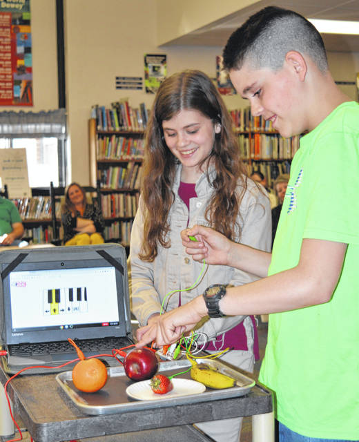 Believe it or not, when you poke these fruit items, you can make music that sounds like a keyboard. The East Clinton Middle School Science Club students are, from left, Carman Brown and Mitchell Ellis.