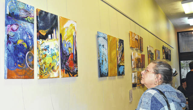 Sue Hicks, right foreground, studies oil paintings on canvas by Elena Raye Clair of Wilmington.