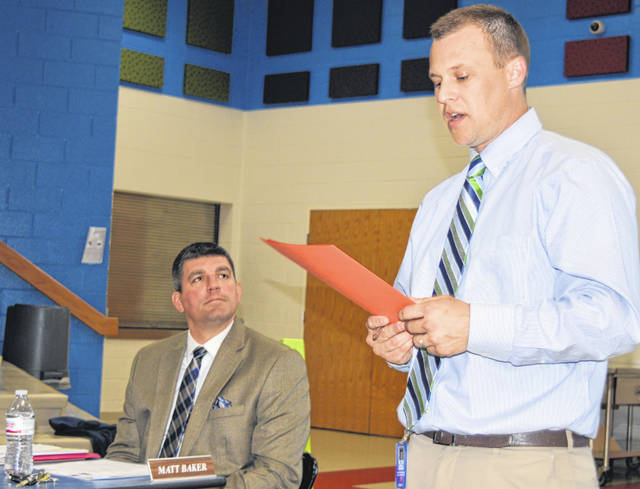 Clinton-Massie High School Principal Aaron Seewer, right foreground, delivers a report at this week's school board meeting. On the left is Superintendent Matt Baker.