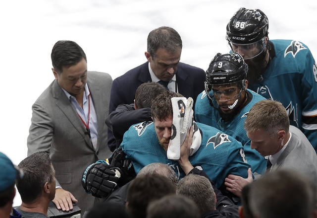 San Jose Sharks center Joe Pavelski, bottom center, is helped off the ice during the third period of Game 7 of an NHL hockey first-round playoff series against the Vegas Golden Knights in San Jose, Calif., Tuesday, April 23, 2019. (AP Photo/Jeff Chiu)