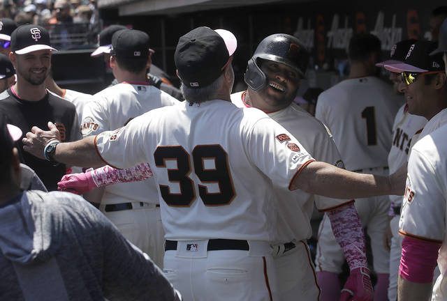 San Francisco Giants' Pablo Sandoval, center right, is congratulated by assistant hitting coach Rick Schu (39) after hitting a two-run home run against the Cincinnati Reds during the first inning of a baseball game in San Francisco, Sunday, May 12, 2019. (AP Photo/Jeff Chiu)