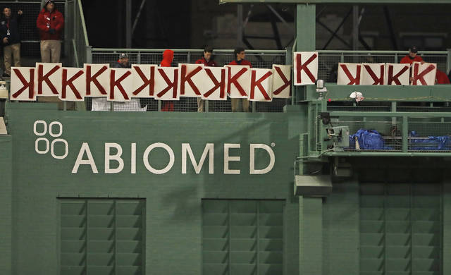 A fan, right, records the 17th strikeout of Boston Red Sox's Chris Sale during the seventh inning of a baseball game against the Colorado Rockies Tuesday, May 14, 2019, at Fenway Park in Boston. (AP Photo/Winslow Townson)