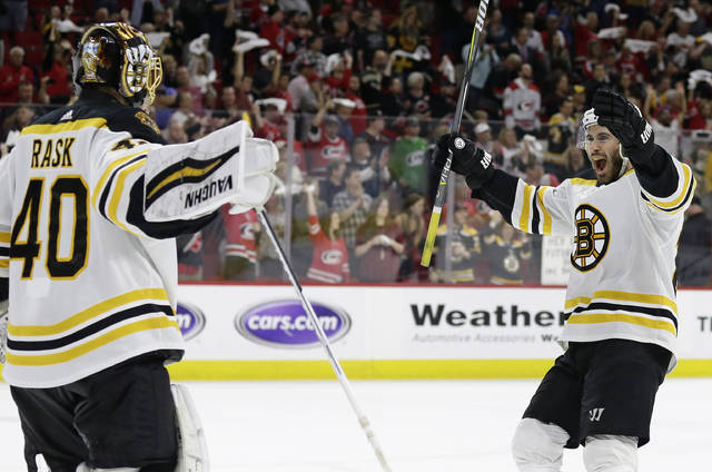 Boston Bruins goalie Tuukka Rask (40), of Finland, celebrates with John Moore following Game 4 of the NHL hockey Stanley Cup Eastern Conference finals against the Carolina Hurricanes in Raleigh, N.C., Thursday, May 16, 2019. Boston won 4-0 to advance to the Stanley Cup Final. (AP Photo/Gerry Broome)