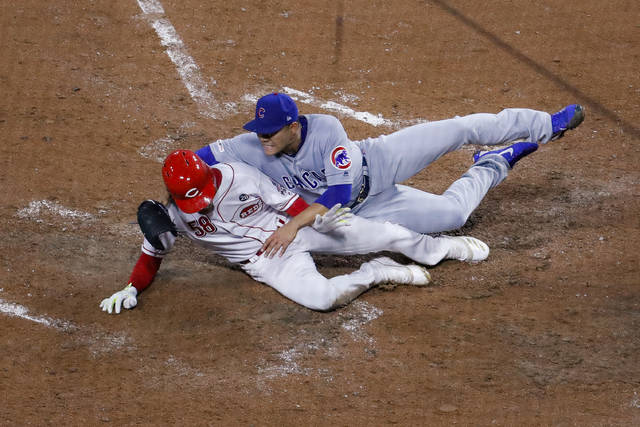 Cincinnati Reds' Luis Castillo (58) scores on a wild pitch by Chicago Cubs starting pitcher Jose Quintana, right, during the fifth inning of a baseball game Thursday, May 16, 2019, in Cincinnati. (AP Photo/John Minchillo)