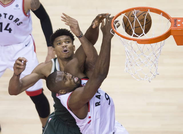 Toronto Raptors center Serge Ibaka battles for the ball against Milwaukee Bucks forward Giannis Antetokounmpo during the second half of Game 4 of the NBA basketball playoffs Eastern Conference finals, Tuesday, May 21, 2019, in Toronto. (Nathan Denette/The Canadian Press via AP)
