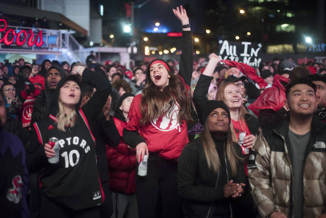 FILE - In this Sunday, May 12, 2019, file photo, basketball fans cheer for the Toronto Raptors before claiming victory over the Philadelphia 76ers outside Maple Leaf Square during the second half of an NBA Eastern Conference semifinal basketball game in Toronto. For Raptors games, Maple Leaf Square, aka Jurassic Park, boasts a college vibe of rowdy fans crammed into an area that covers two city blocks. (Tijana Martin/The Canadian Press via AP, File)