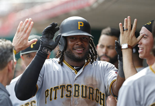 Pittsburgh Pirates' Josh Bell (55) celebrates a three-run home run off Cincinnati Reds relief pitcher Michael Lorenzen in the dugout during the seventh inning of a baseball game, Wednesday, May 29, 2019, in Cincinnati. (AP Photo/Gary Landers)