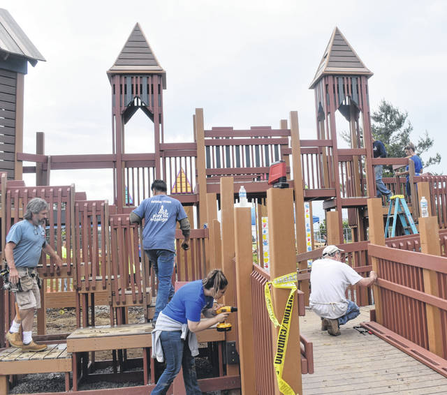 The community storms the new castle playground on Thursday at David Williams Park in the hopes of finishing it over the weekend.