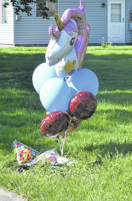 Balloons, flowers and candy are among the items at a makeshift memorial for Michael Melvin who was shot on Grant Street in Wilmington early Tuesday morning.