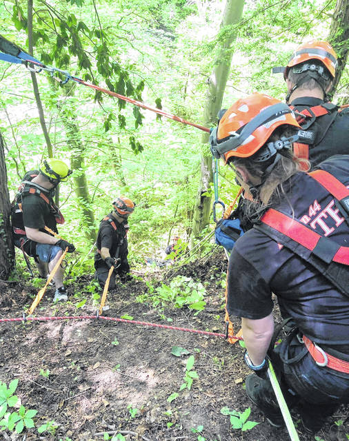 Emergency personnel are shown bringing a body up the side of a cliff Monday on Cave Road.