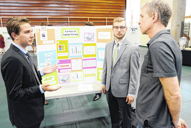 """From left, junior Gabriel Nygard and Connor Wichmann discuss their research and data analysis titled """"Factor of Laptop Pricing"""" with Dr. Michael Snarr, professor of political science."""