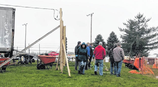 Even the cold, drizzling weather can't deter the volunteers from working on the construction of the new playground at David Williams Park on Monday.