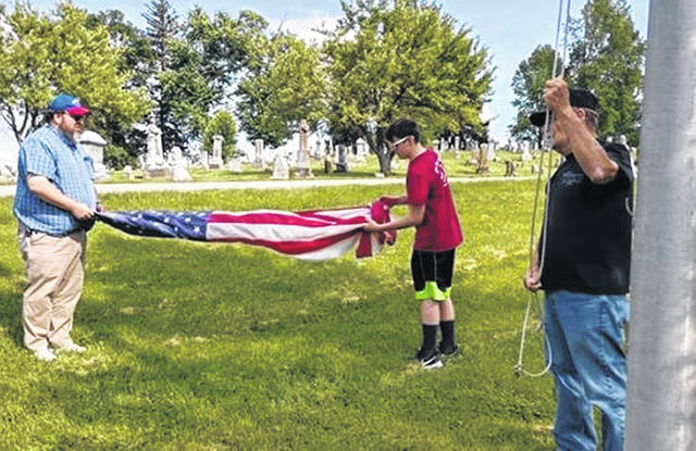 Mike Daugherty, left, and Boy Scout Josiah Daugherty from Troop 999 fold the tattered flag removed from the pole, where Allen Wood stands. On Tuesday evening, Troop 999 held a flag retirement ceremony and honorably retired all the old flags in accordance with the United States Flag Code.